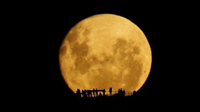 Vidéo : silhouettes humaines sur un lever de Lune en temps réel.